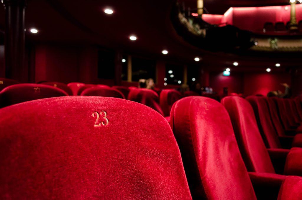 Asientos rojos en una sala de cine. Las APIs y el software de gestión nos puede facilitar muchísimas tareas.